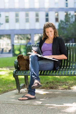 Mid adult female student with digital tablet and book studying on bench at university campus photo