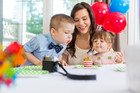 Family with birthday boy blowing out candle on cupcake at home photo