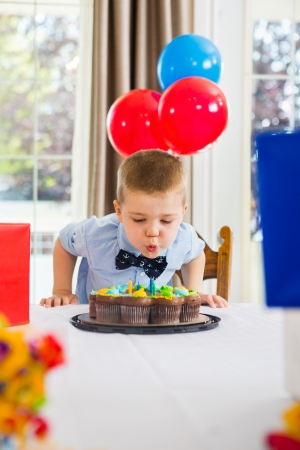 Boy blowing candles on birthday cake at home photo