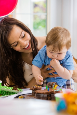 Happy mother looking at baby boy eating cupcake at birthday party photo