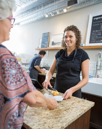 Smiling female cafe owner serving sweet food to senior woman at counter photo