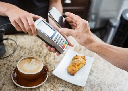 カフェのカウンターで電子ブック リーダー以上の携帯電話を介して払ってお客様の画像をトリミング 写真素材