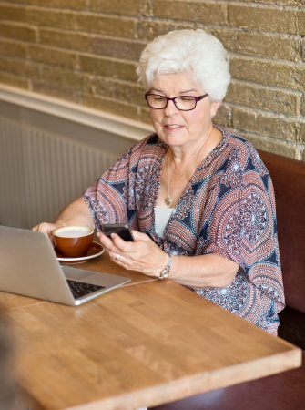 Senior woman with laptop and coffee cup text messaging through smartphone in cafe photo