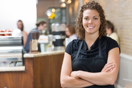 Portrait of happy mid adult female owner standing arms crossed in cafe photo