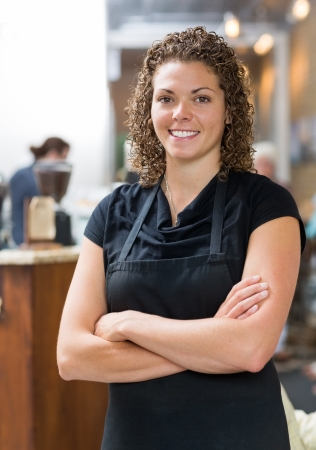 Portrait of confident mid adult waitress standing arms crossed in cafeteria photo