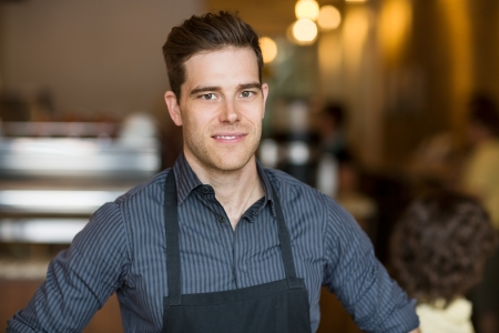 Portrait of smiling young male owner standing in cafe Stock Photo
