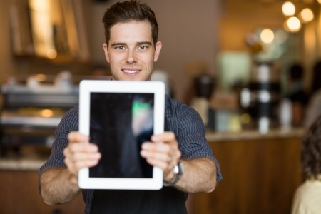 Portrait of male cafe owner holding digital tablet in restaurant photo