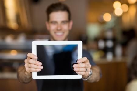 shop owner: Male cafe owner showing digital tablet in cafeteria