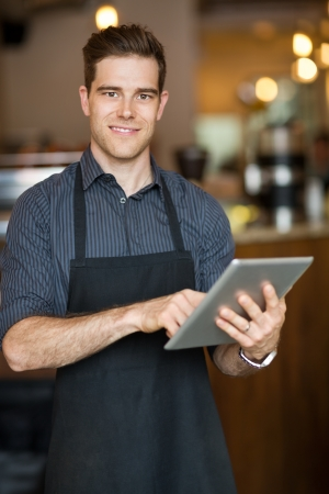 Portrait of smiling male owner holding digital tablet while standing in cafeteria photo