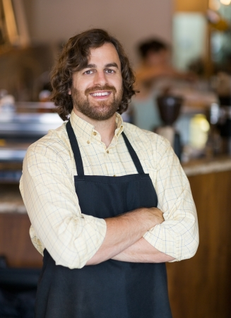 folded hands: Portrait of happy mid adult male owner standing arms crossed in cafeteria