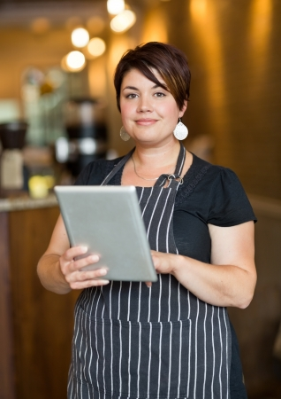 Portrait of beautiful female owner holding digital tablet while standing in cafeteria photo