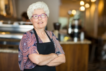 coffeeshop: Portrait of smiling senior female owner standing arms crossed in coffee shop