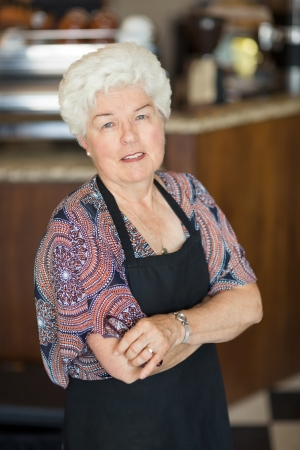 Portrait of confident senior female owner standing arms crossed in coffeeshop photo