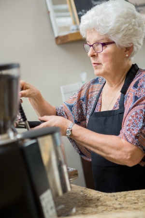 Senior barista working espresso machine in cafe photo