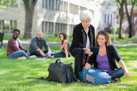 university text: Female university students using digital tablet on campus park with friends studying in background