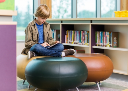 Full length of schoolboy using digital tablet on seat in library photo