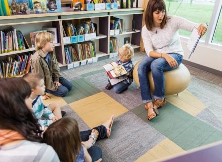 persona leyendo: Profesor joven que lee el libro a los niños en la biblioteca de la escuela primaria