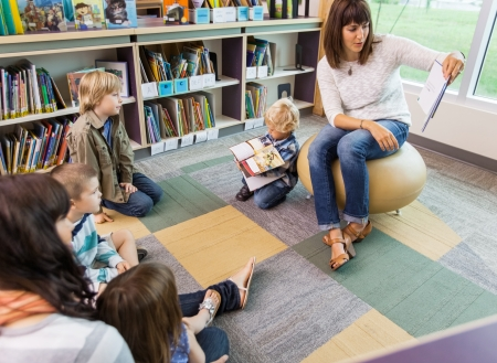 sitting area: Young teacher reading book to children in library of elementary school Stock Photo