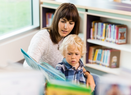 Elementary student with teacher reading book in school library photo