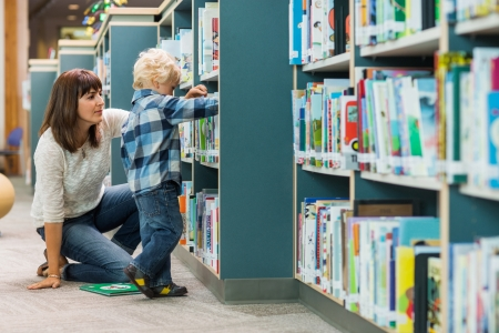 assisting: Young teacher assisting boy in selecting book from bookshelf in school library