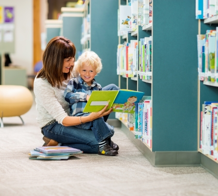public library: Full length of smiling boy and teacher reading book by bookshelf in library
