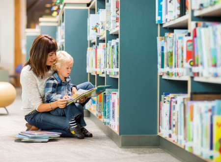 Elementary student with teacher reading book by bookshelf in library photo