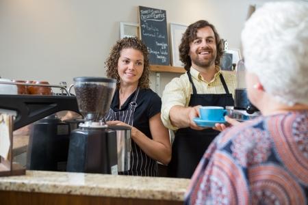 business smile: Propietarios de caf� sonrientes sirviendo caf� a la mujer mayor en el mostrador Foto de archivo