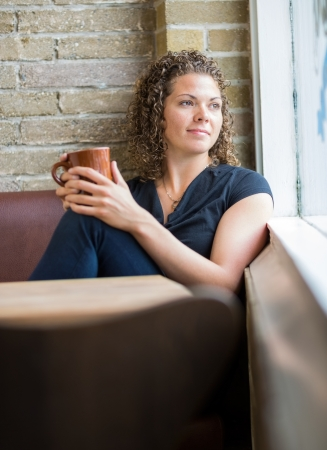 looking through window: Thoughtful woman with coffee mug looking through window in cafeteria Stock Photo