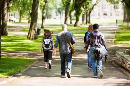 大学生のキャンパスの道の上を歩いてのバックパックの背面図