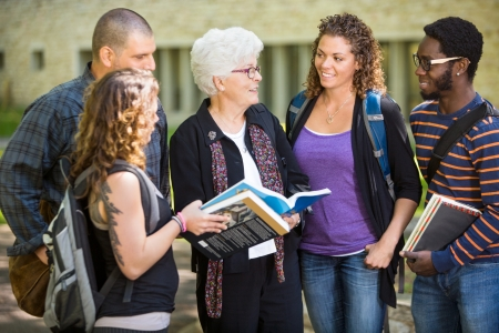 education help: Group of university students with books studying on campus