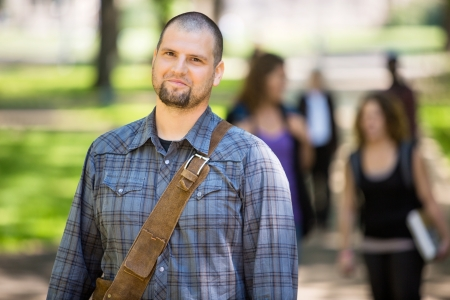 waistup: Portrait of confident male student at campus with friends in background Stock Photo
