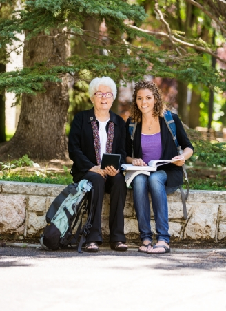 Full length portrait of professor helping female student with digital tablet photo