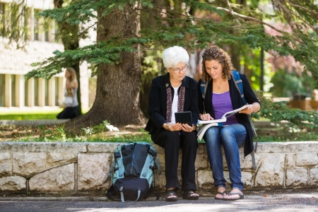 Full length of female student studying on campus with professor helping photo