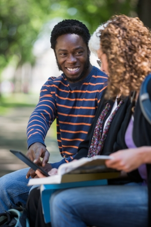 Happy male university student using digital tablet with female friends on campus photo