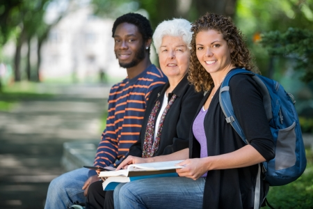 Portrait of confident multiethnic university students sitting on campus photo