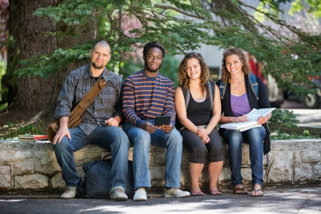 Portrait of confident multiethnic university students sitting on parapet at campus photo
