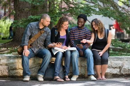 Multiethnic university students using digital tablet while studying on parapet at campus photo