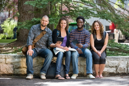 Full length portrait of multiethnic students sitting on parapet at university campus photo