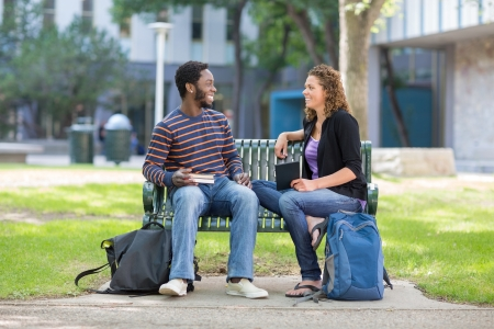 Happy male and female students sitting on bench at university campus photo