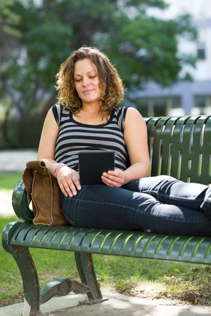 Mid adult female student using digital tablet while relaxing on bench at university campus photo
