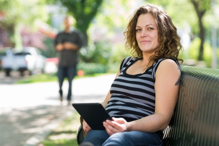 Portrait of confident female student relaxing on bench at university campus photo