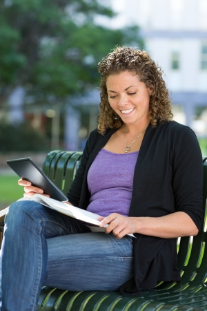 Happy female university student with digital tablet studying on bench at campus photo