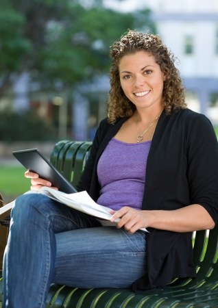 Portrait of happy female student with book and digital tablet sitting on bench at university campus photo