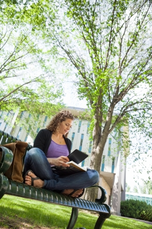 Female university student using digital tablet while studying on bench at campus photo