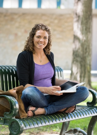Portrait of happy female student studying on bench at university campus photo