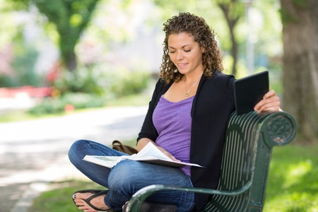 Female university student reading book on bench at campus photo