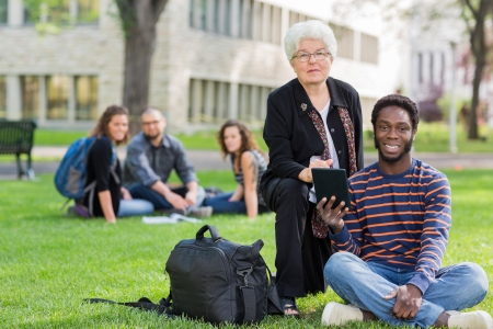 Portrait of professor and student outdoors on university campus with friends in background photo