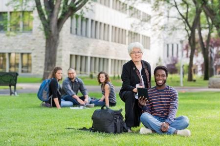 college professor: University Professor assisting grad student with small digital tablet Stock Photo