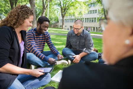 Group of multiethnic university students using digital tablet on campus park photo