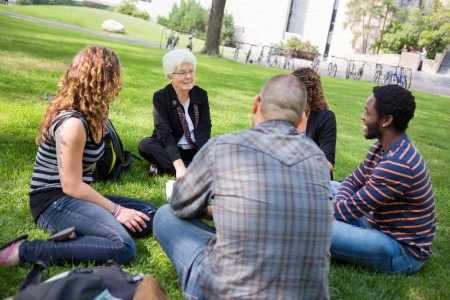 Senior female university professor teaching students outdoors Standard-Bild